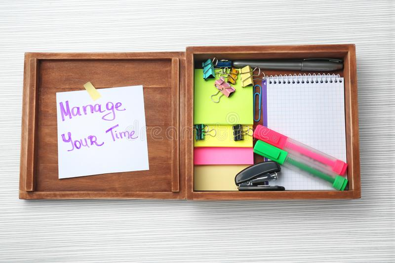 Wooden box with written phrase \'Manage your time\' on paper sheet and stationery on table. Time management concept royalty free stock photos
