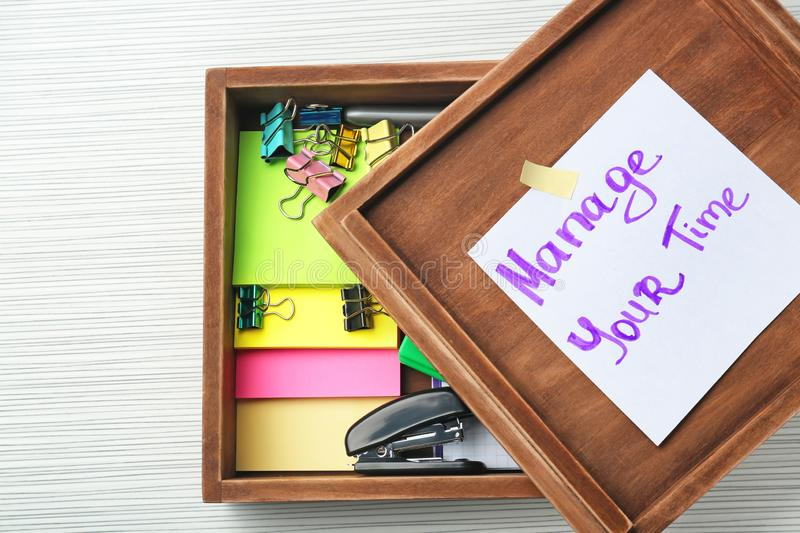 Wooden box with written phrase \'Manage your time\' on paper sheet and stationery on table. Time management concept royalty free stock photo