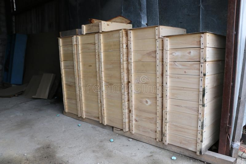 Wooden boxes for internal bee hives on a large apiary. Several rows of wooden boxes for the internal arrangement of bee hives on a large apiary stock photo