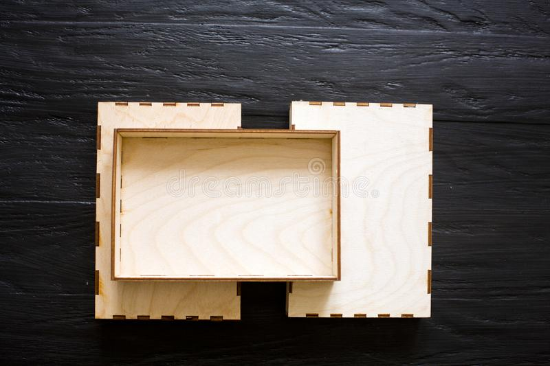Wooden boxes of plywood on a black wooden background. royalty free stock images