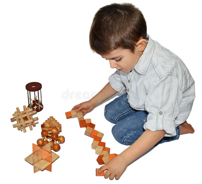 Wooden Brain Teaser. Boy with many wooden logic toys stock images