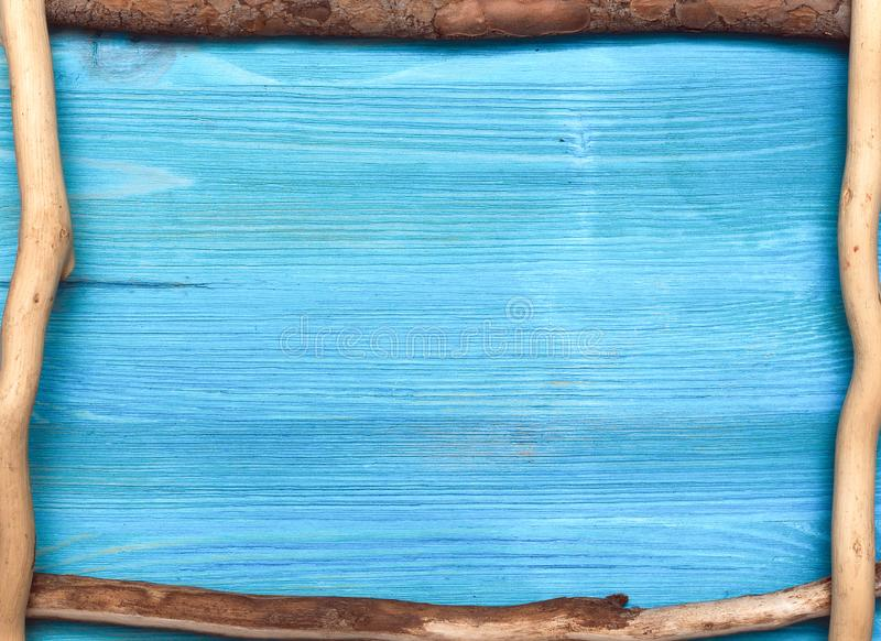 Wooden frame. Wooden branch frame on a blue board flat lay background with copy space, tree, nature, natural, backdrop, timber, table, texture, abstract, dry royalty free stock photography