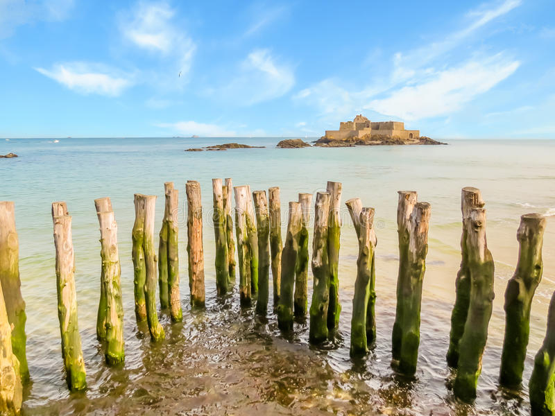Wooden breakwaters in high flow and Fort National royalty free stock images