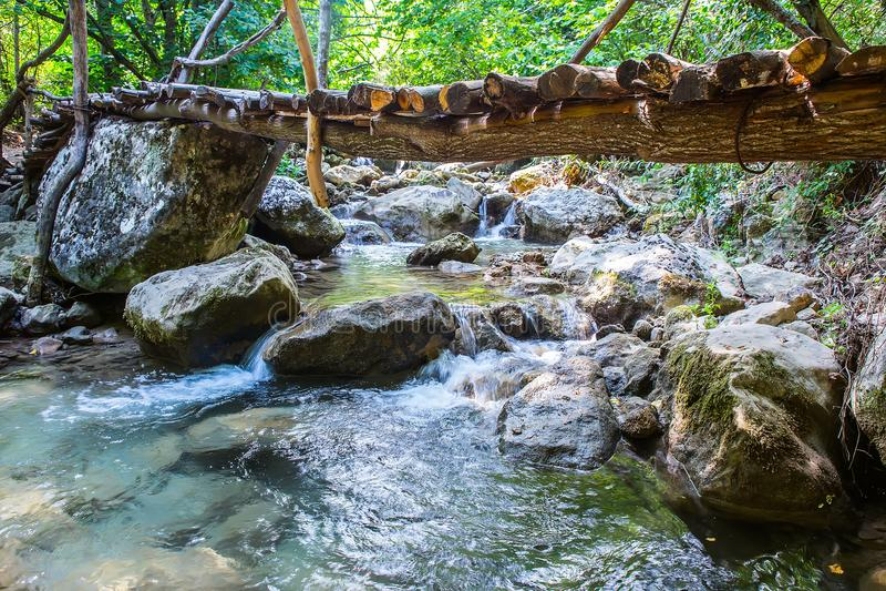 Wooden bridge across stream. royalty free stock photo