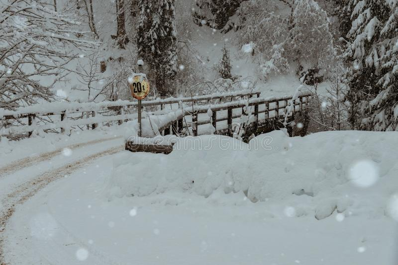 Wooden bridge in the austrian alps, covered with snow. During a blizzard stock image