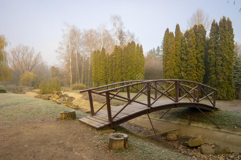 Wooden bridge in autumn park. Misty foggy autumn day royalty free stock image
