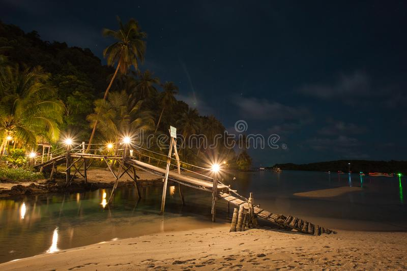 Wooden bridge on the beach at night time. royalty free stock photography
