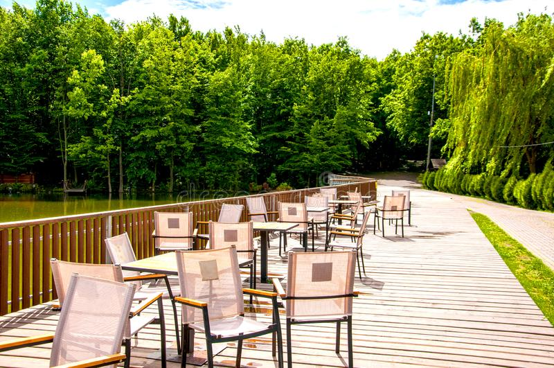 Wooden bridge with a fence on which tables and chairs are located. Summer cafe. It`s summer outside. The sun is shining. On the background of green forest royalty free stock photos