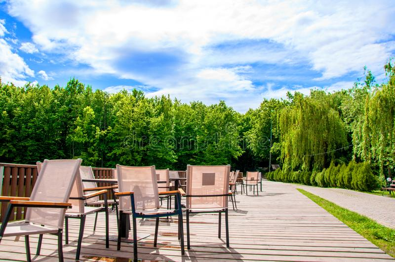 Wooden bridge with a fence on which tables and chairs are located. Summer cafe. It`s summer outside. The sun is shining. On the background of green forest royalty free stock images