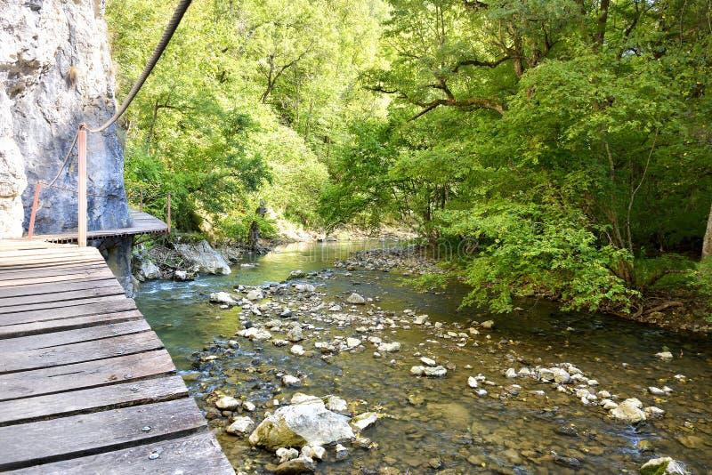 The Wooden bridge leading around rock cliff. Wooden bridge leading around rock cliff stock photography
