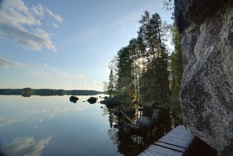 Wooden bridge leading around rock cliff at Faangsjoen in Sweden.  royalty free stock images