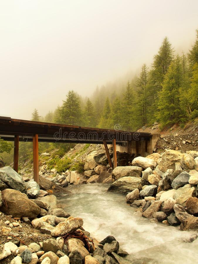 Wooden bridge over Alps rapids on quick mountain river in Alps stock images