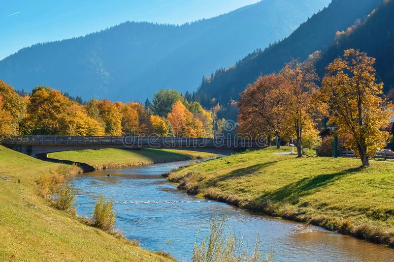 Wooden bridge over calm river in an autumn park with orange trees in the mountains in Alps royalty free stock photos
