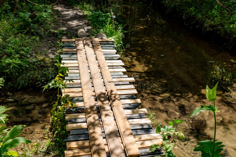 Wooden bridge over a forest stream. Outdoor royalty free stock photo