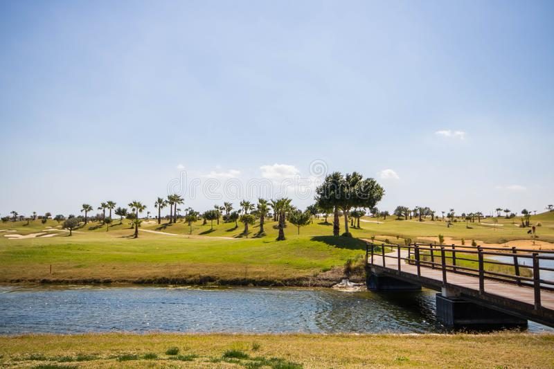 Wooden bridge over the lake in a golf course on a summer day with clear blue sky. Wooden bridge over the lake and path going through a golf course in Spain on a stock images