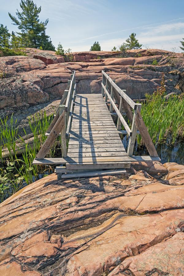 Wooden Bridge over Rock Outcrops stock images
