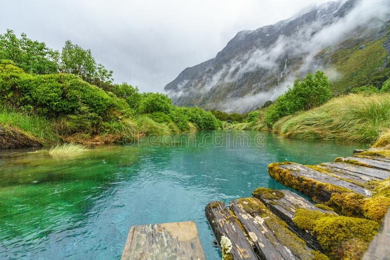 Wooden bridge over river in the mountains in the rain, new zealand 5 royalty free stock photography
