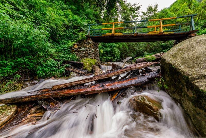 Wooden bridge over waterfall in himalayas - sainj, kullu, himachal, India. Photo of wooden bridge over waterfall in himalayas - sainj, kullu, himachal, India royalty free stock photo