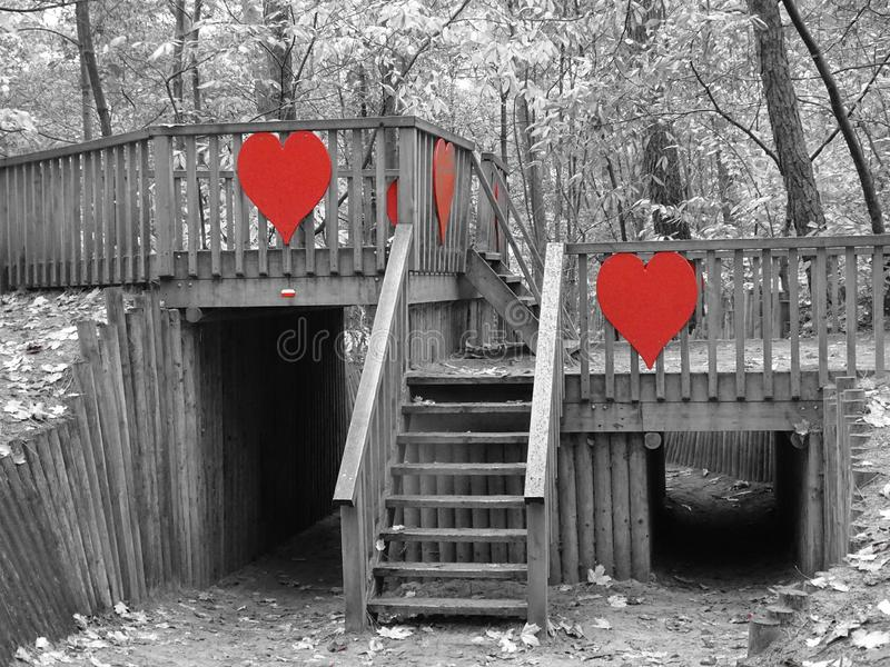 Wooden bridge with red hearts in forest. Grey scale playground kids royalty free stock photo
