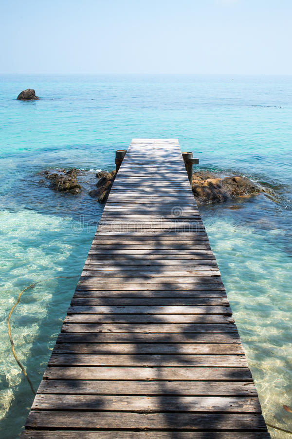 Wooden bridge to the sea stock images