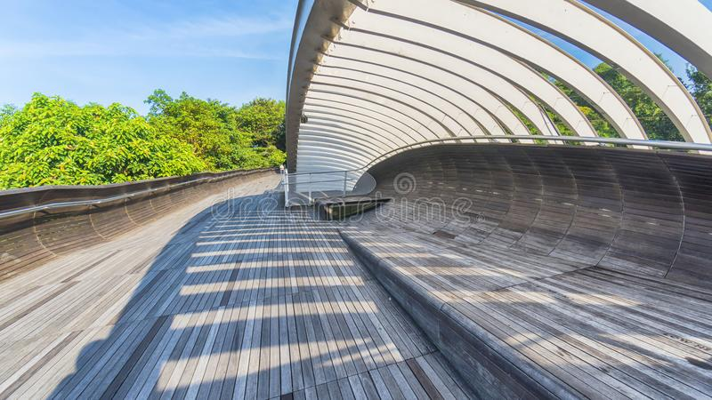 wooden bridge walkway with shadow of steel structure from sunlight with forest tree green field and blue sky white cloud royalty free stock photo