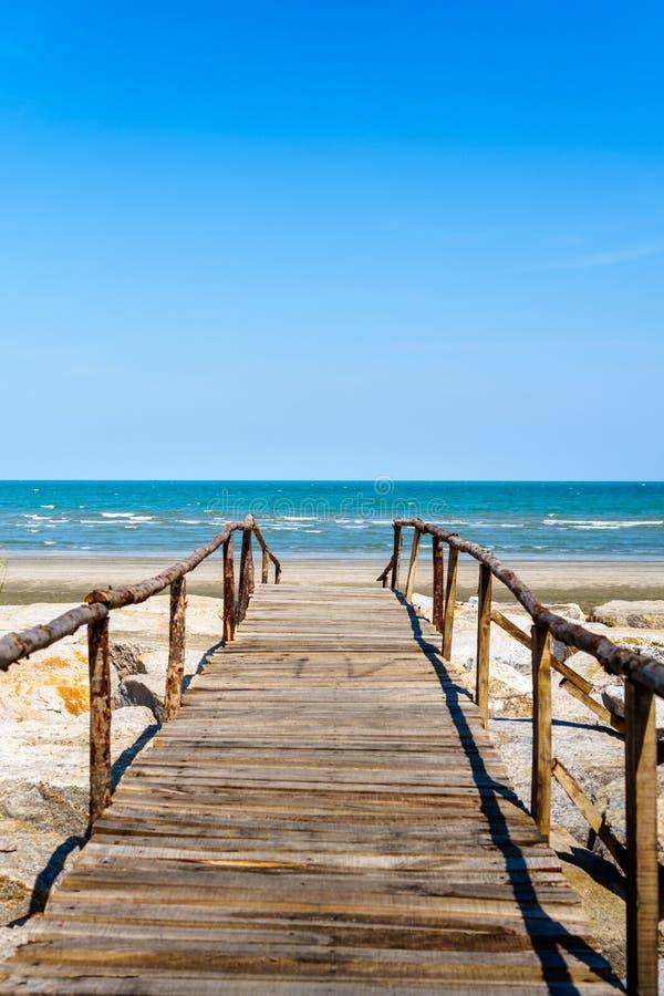 Wooden bridge walkway to the sea beach. On blue sky background stock image