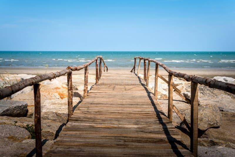 Wooden bridge walkway to the sea beach. On blue sky background stock photo