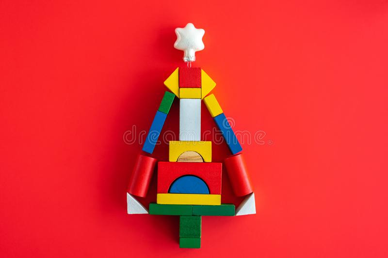 Wooden bright geometric shapes, Creative christmas tree. Wooden bright geometric shapes, multi colored education toy for kid on red paper. Creative abstract stock images