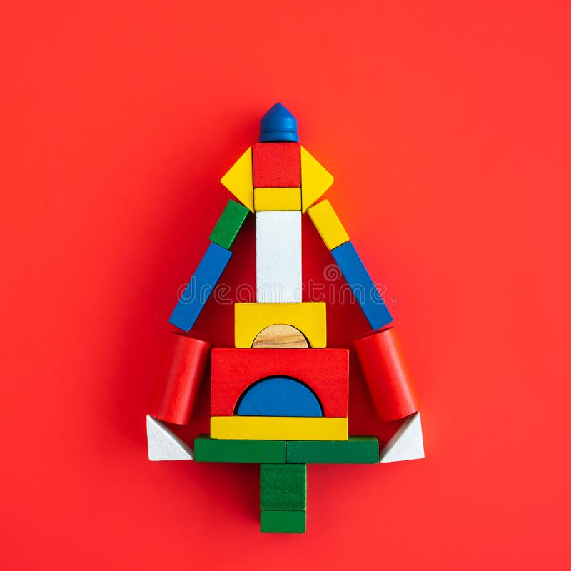 Wooden bright geometric shapes, multi colored education toy for kid. On red paper background, block, abstract, minimalism, creative, minimalistic, square, blue royalty free stock photography