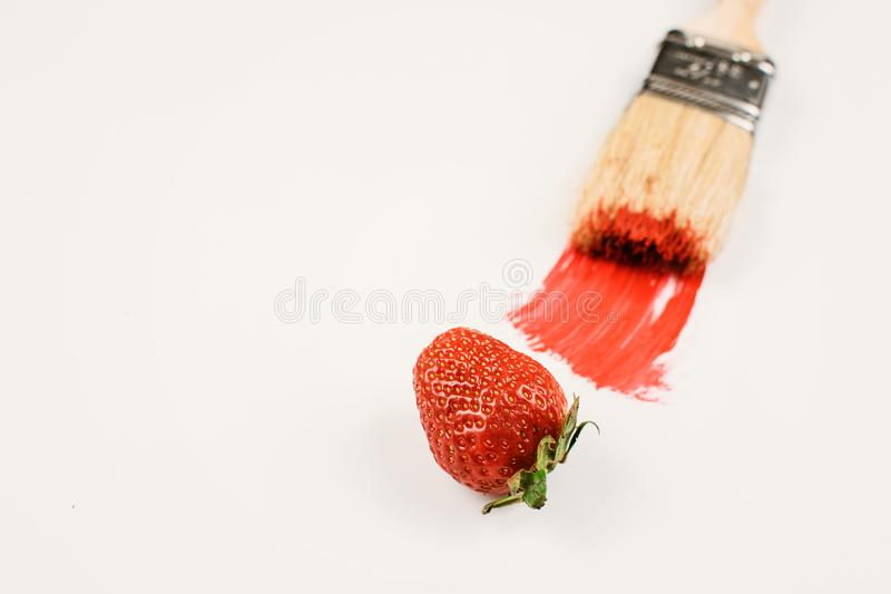 Wooden bristle painting brush with red paint and red fresh strawberry on white background. Modern art, minimal style royalty free stock image