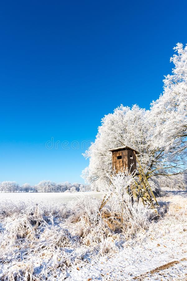 Wooden brown hunting hideout next to frozen trees stock photos