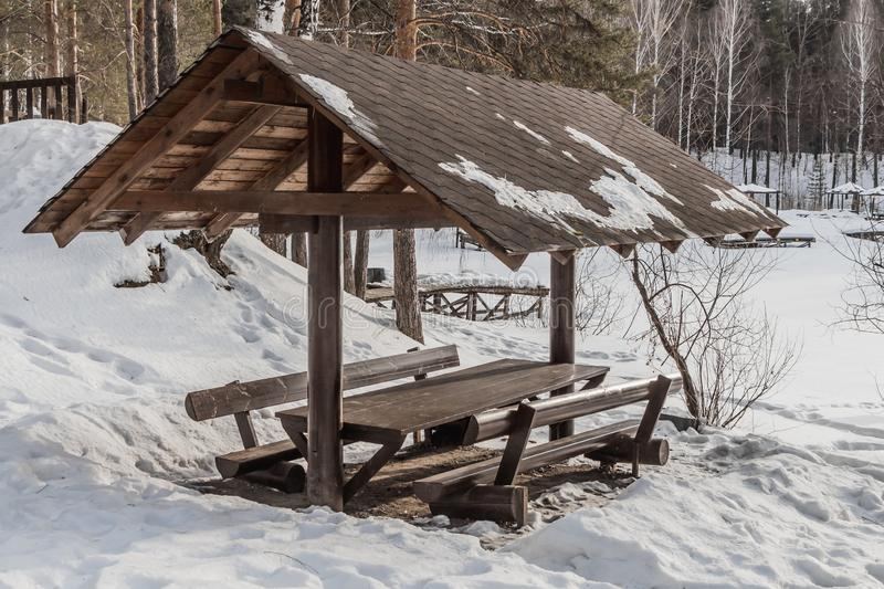 A wooden brown pavilion with table and benches with white snow on the roof in winter in pines and birches forest with a pond stock photos