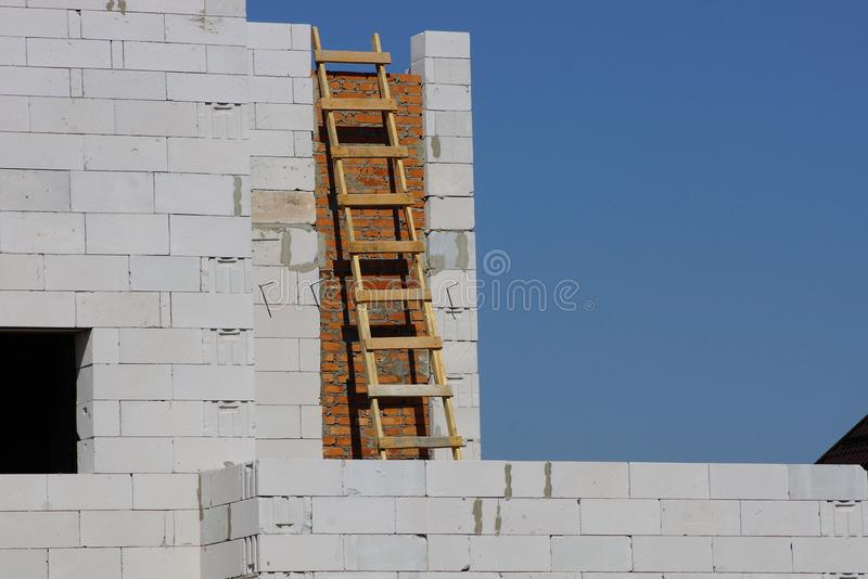 Wooden brown staircase by the gray brick wall of an unfinished house against the blue sky royalty free stock photo