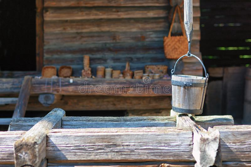 Wooden bucket by the well. Wooden bucket with iron hoops on the well of a crane against the background of an old house royalty free stock photography