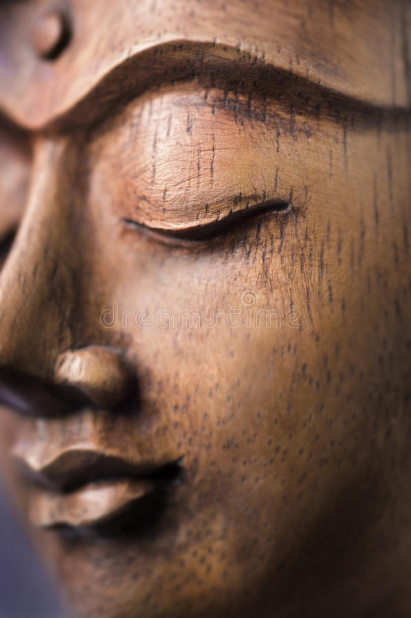 Wooden Buddha Face. Beautiful composition and mystical lightning on the meditating Buddha Shakyamuni stock photos