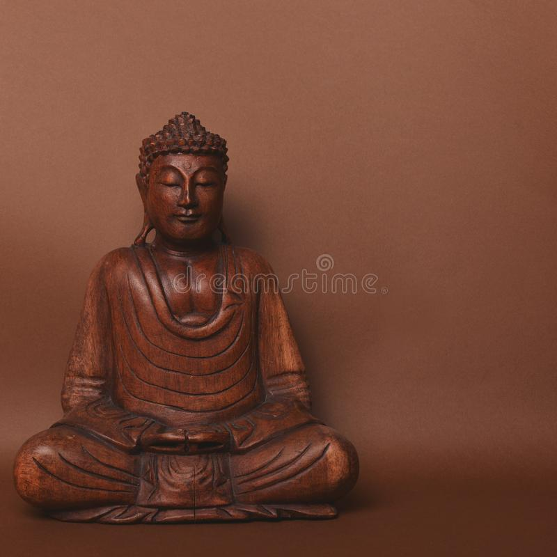 Wooden buddha statue against brown backgound stock photography