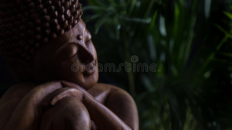 Wooden buddha statue and light royalty free stock image