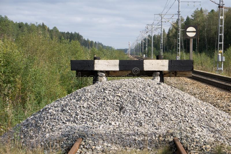 Wooden buffer stop with red stop sign ending rail tracks concept for limit, limitation restriction boundary, prohibited, end , bor royalty free stock image