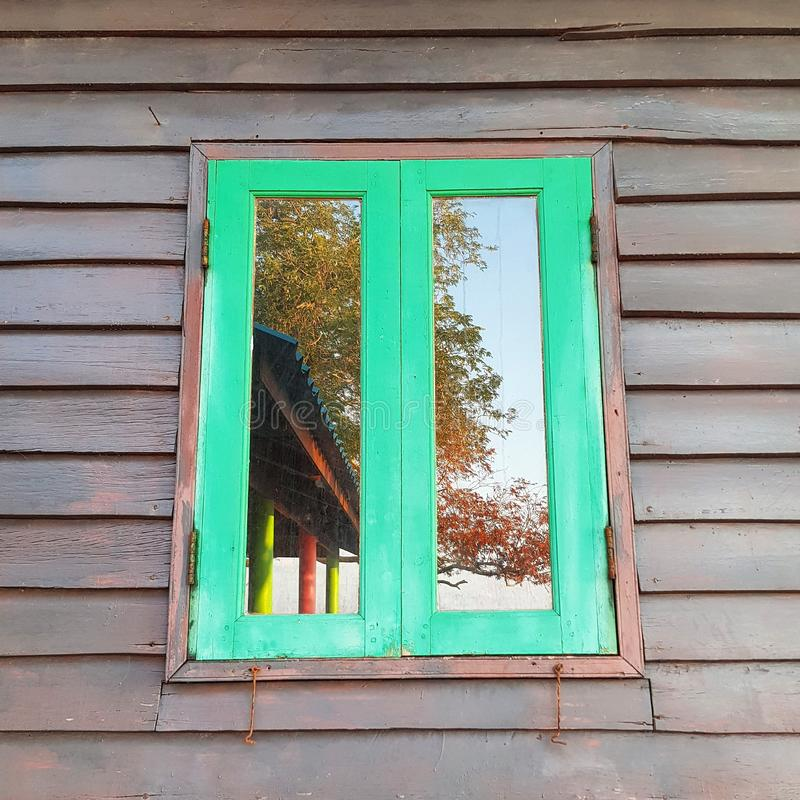 Wooden building with glass window. Wooden building glass window  home house architecture old vintage design background frame wall green exterior closed stock photo