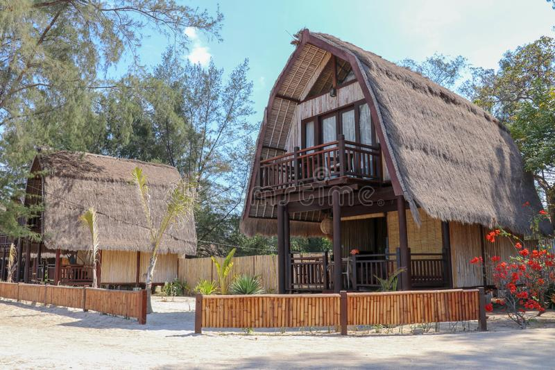 Wooden bungalow on white sand beach in tropical paradise. Wooden cottage with a reed roof on the island of Gili Meno in Indonesia. royalty free stock photo