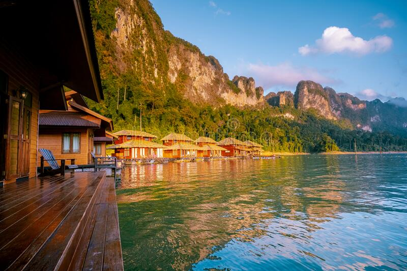 Wooden bungalows on tropical shore in the Chiew Lan Lake, Khao Sok national park, Thailand. Lake stock photography