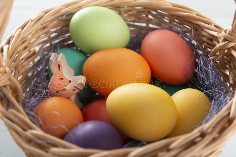 Wooden bunny in a withe basket with colorful Easter eggs royalty free stock photos