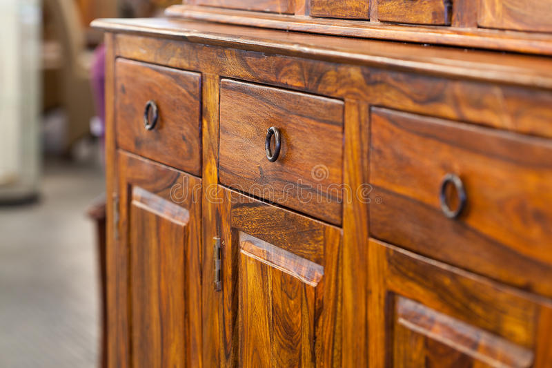 Wooden cabinet. A closeup od a dark brown wooden cabinet with drawers stock image