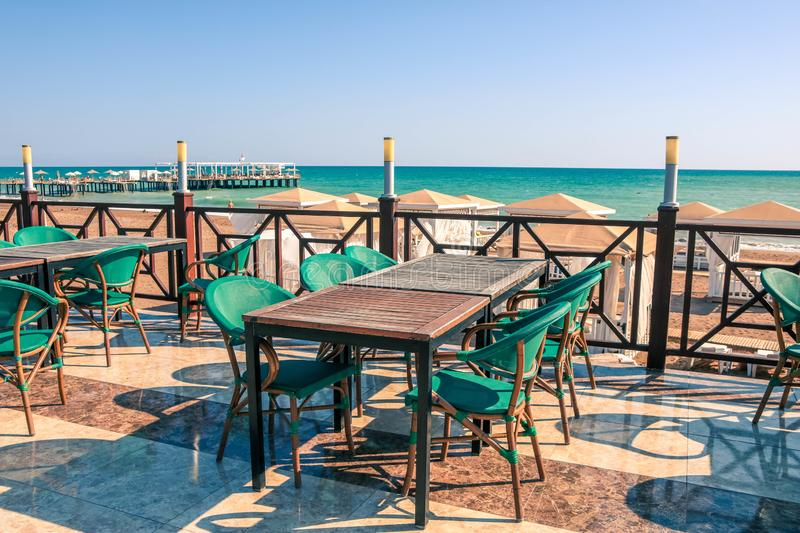 Wooden cafe table and chairs on a tropical beach with blue sea on background stock images