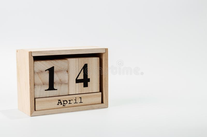 Wooden calendar April 14 on a white background. Close up royalty free stock photo