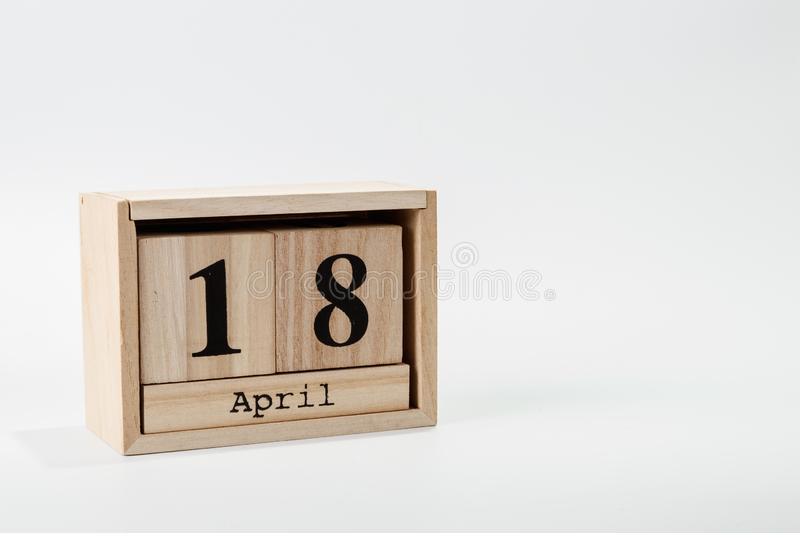 Wooden calendar April 18 on a white background. Close up royalty free stock photography