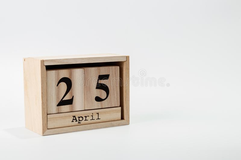 Wooden calendar April 25 on a white background. Close up royalty free stock photography