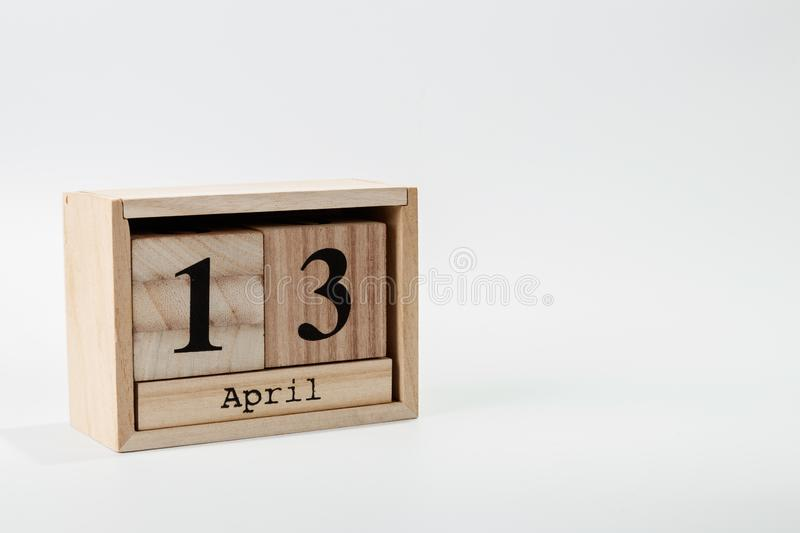 Wooden calendar April 13 on a white background. Close up stock photo