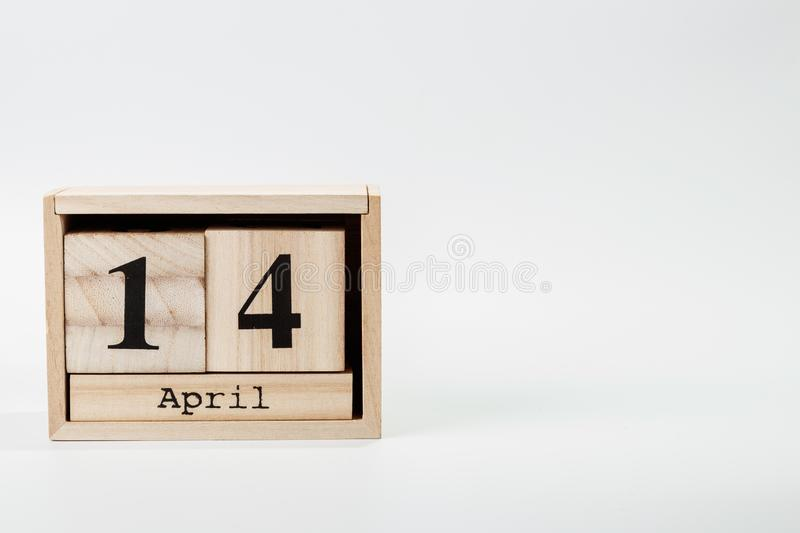 Wooden calendar April 14 on a white background. Close up stock photography