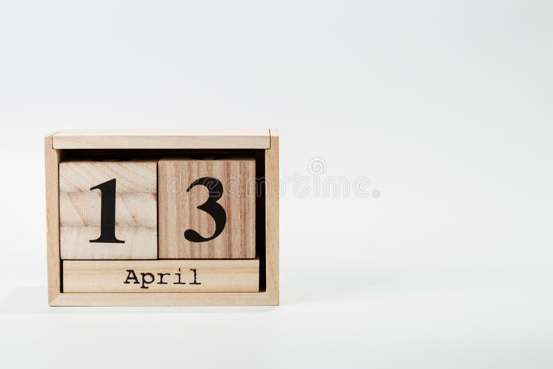 Wooden calendar April 13 on a white background. Close up royalty free stock photo